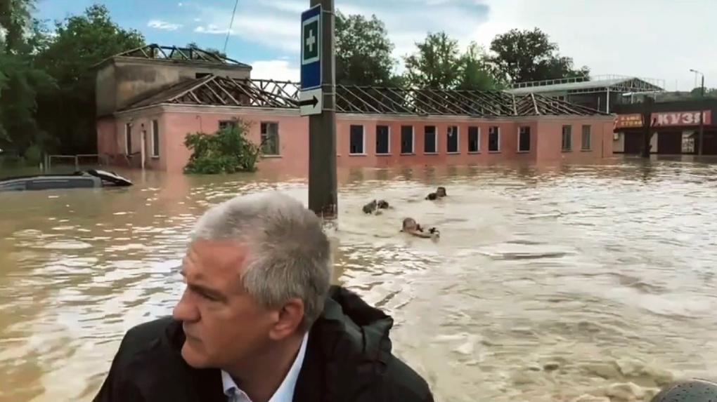 Глава Крыма на лодке осматривает затопленные улицы, а за ним кролем плывут трое мужчин. Что происходит?